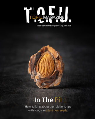 "Image contains a dark background with a peach pt in the middle. The pit has been cut open to show the light brown seed. Above the pit, there is text that says ""T.O.F.U."" in white, and within that text there is more text that says ""T.O.F.U. Magazine"". Just below the white T.O.F.U., there is text that says ""There is an alternative 